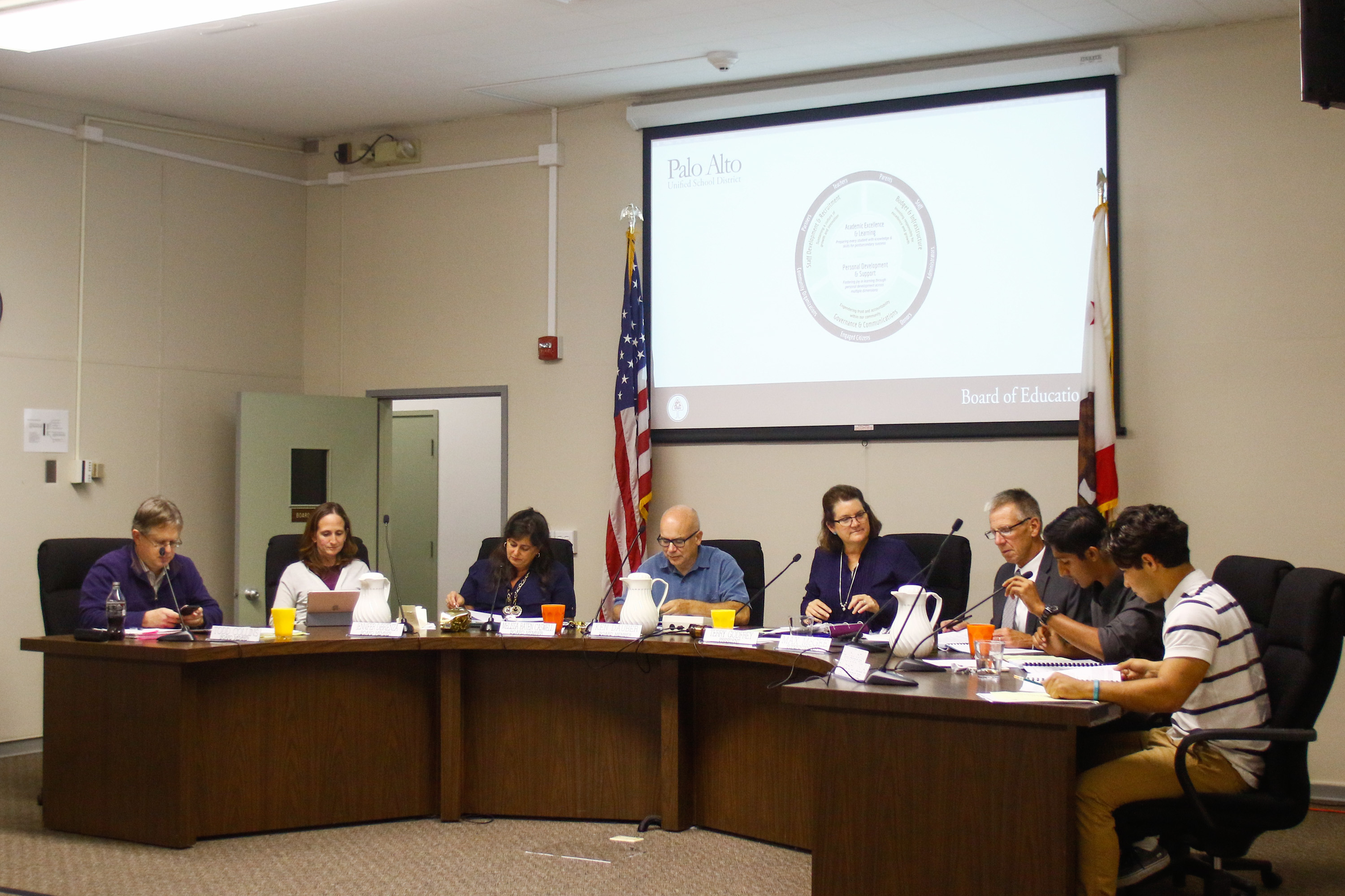 The Palo Alto School Board, from left, board members Todd Collins, Jennifer Dibrienza, Melissa Baten Caswell, Ken Dauber, Board President Terry Godfrey, Superintendent Max McGee, and student representatives Advait Arun and Richy Islas, talk during a board meeting on Sept.13, 2017. Photo by Veronica Weber.