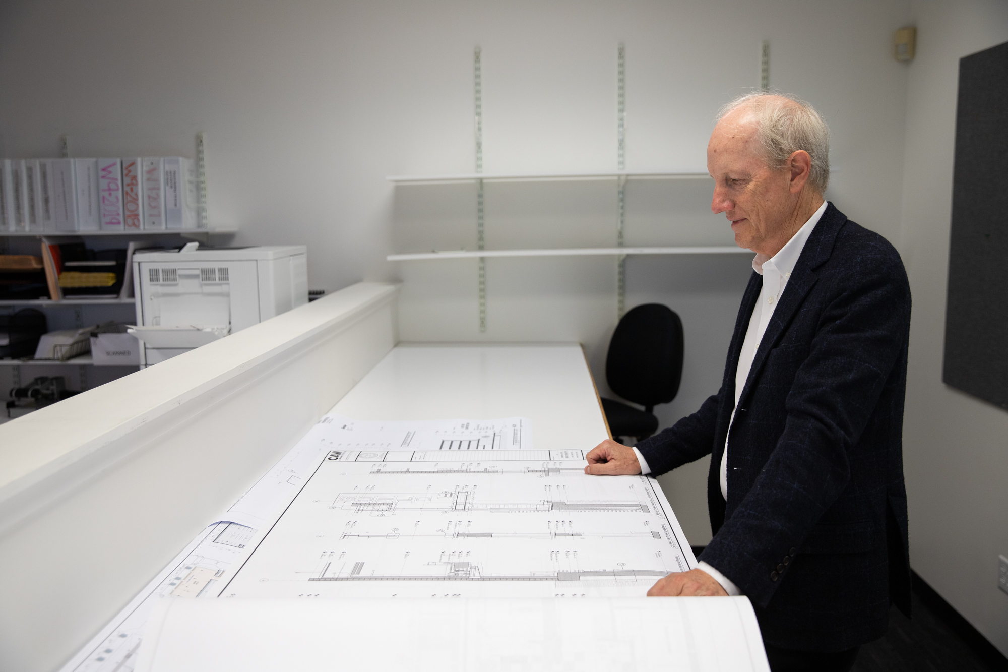 Loren Brown, a third-generation owner of Vance Brown Builders, looks at blueprints for a remodel of the Guild Theatre in Menlo Park on Oct. 2. Photo by Magali Gauthier.
