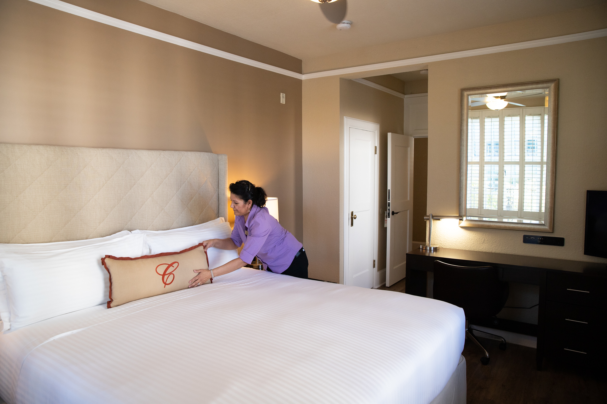 Ninfa Polanco, housekeeping supervisor at the Cardinal Hotel, places a pillow on a bed. The hotel's rooms were given a new look during a renovation in 2013-14. Photo by Magali Gauthier.