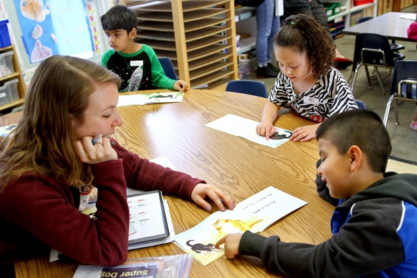 Barron Park Elementary School kindergarten teacher Athena Foley reads with Yeshua Hernandez Aristeo as fellow students Eli Atayde, center, and Arman Hashemi, top left, read on their own during a full-day kindergarten class in 2016. Photo by Veronica Weber.