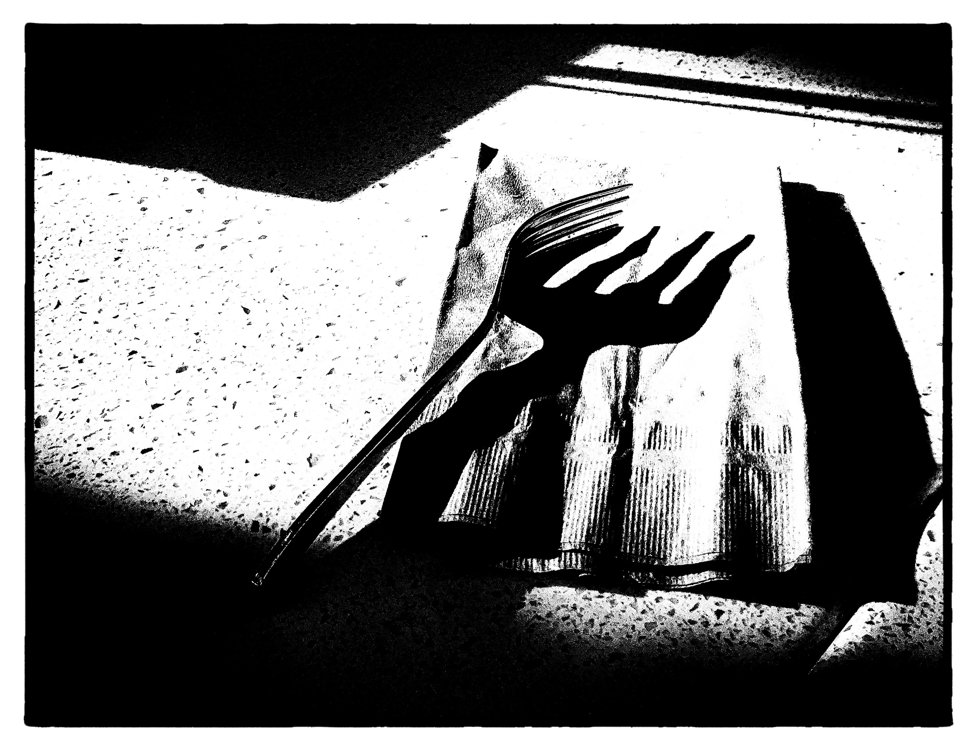 """Artist comments: """"I captured this with my iPhone while waiting for dinner at an outdoor cafe in Mountain View. It was sundown, and I was attracted by the strong shadows cast by the fork on the napkin. The monochrome and 'noir' rendition was created in post-processing. This evoked the title."""""""