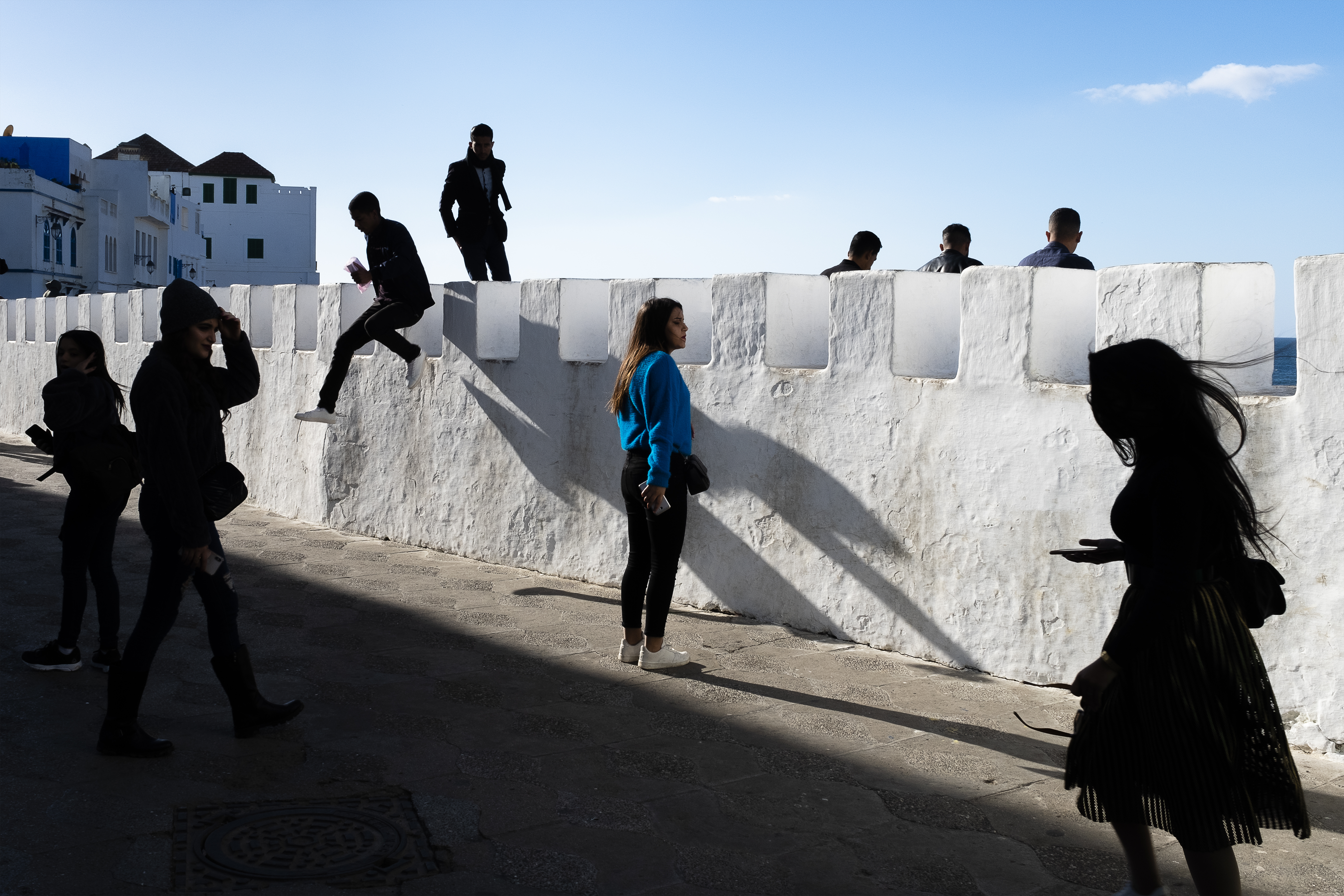 """Artist comments: """"A woman looks peacefully into the abyss of the ocean in a still and contemplative glance while bathed in early evening sunlight as people around her create movement in all directions in Asilah, Morocco."""""""