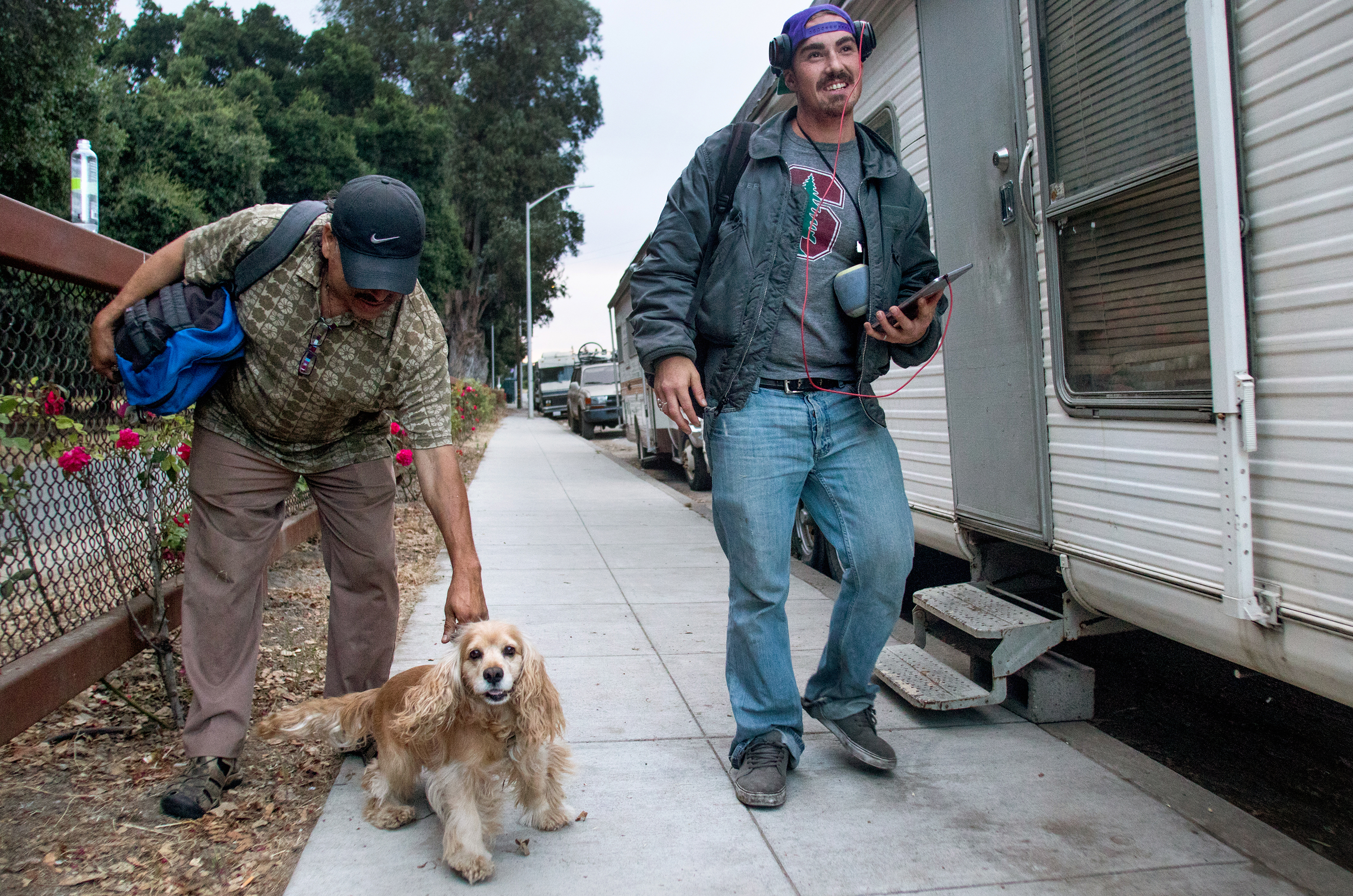 Aleman Cruz Francisco, left, with his dog, Galaxy, and Jacob Tyo, right, step outside of the RVs they occupy on El Camino Real.
