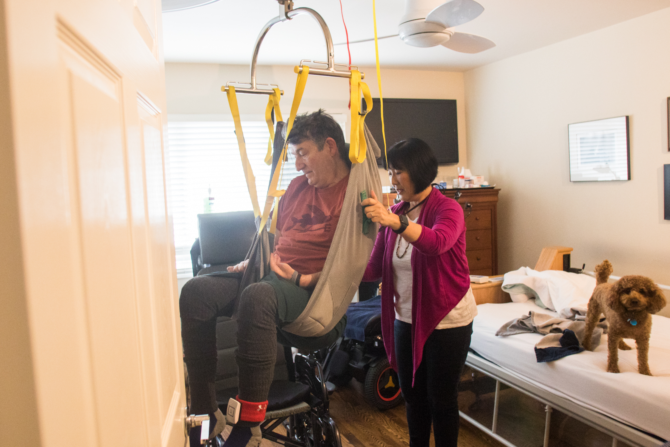 Karen Kang uses a mechanized lift to lower Jon Ferraiolo into his wheelchair as the couple gets ready to step outside for a walk on March 8. Kang says that the family had to completely remodel the lower unit of their house to accommodate Ferraiolo's equipment. They installed the lift, a moveable bed that rotates Ferraiolo throughout his sleep, a wheelchair-accessible bathroom and a lot of equipment.
