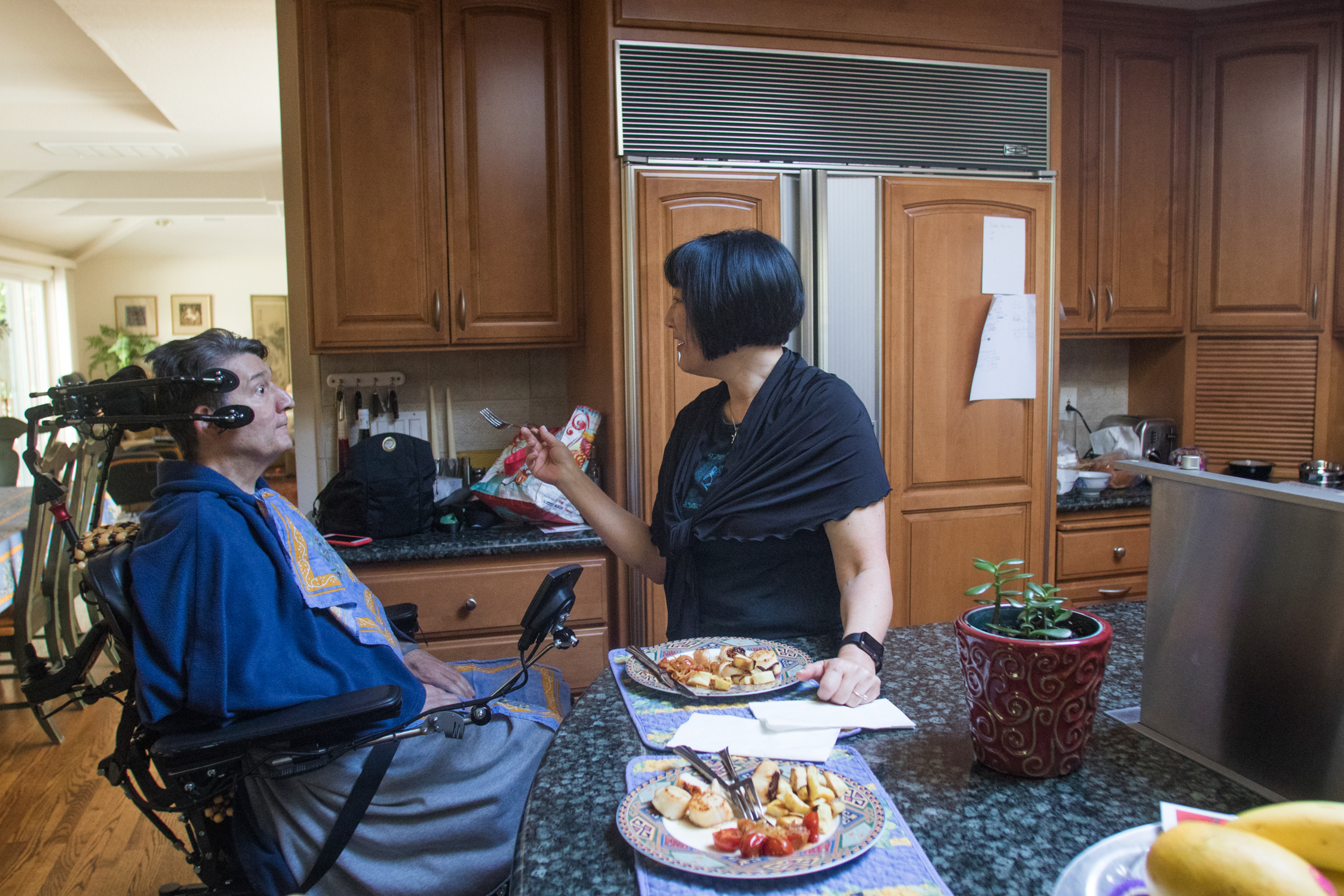 After preparing a dinner of scallops, sweet potatoes, grilled tomatoes and fennel, Karen Kang feeds Jon Ferraiolo at the kitchen counter on April 27, 2018.