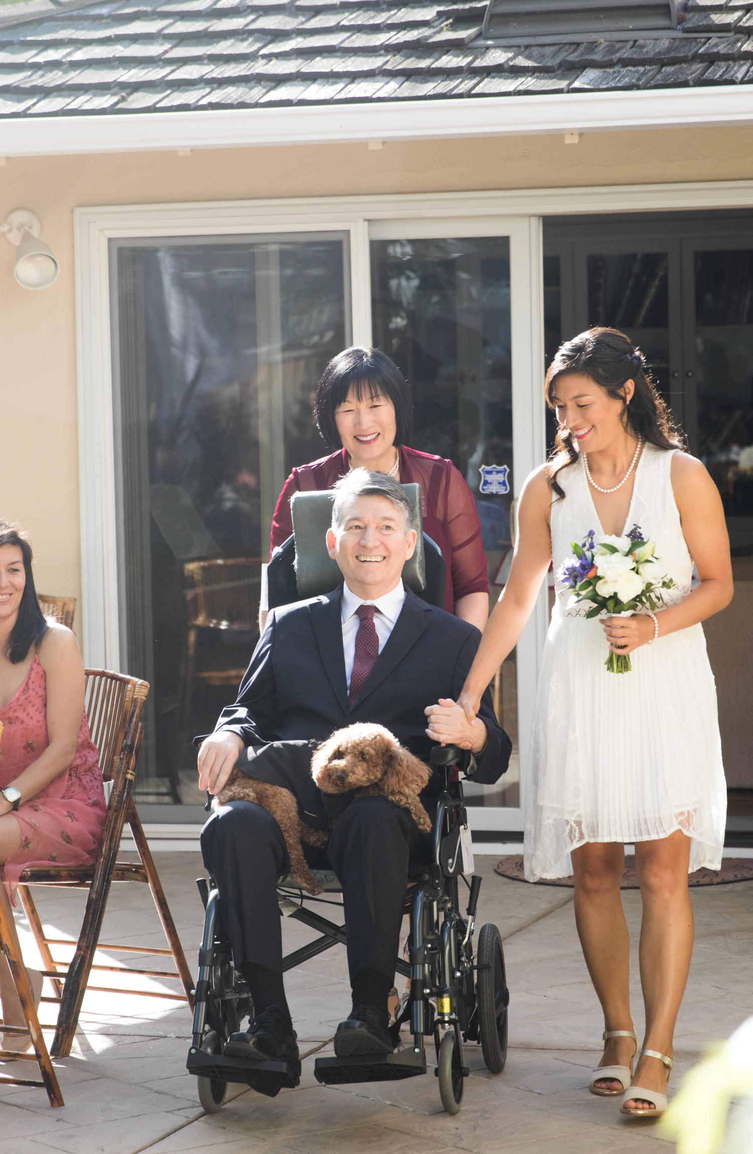 Karen Kang pushes Jon Ferraiolo as he escorts his daughter Natalie Ferraiolo down the aisle during her wedding on April 14, 2018 at their home in Palo Alto.