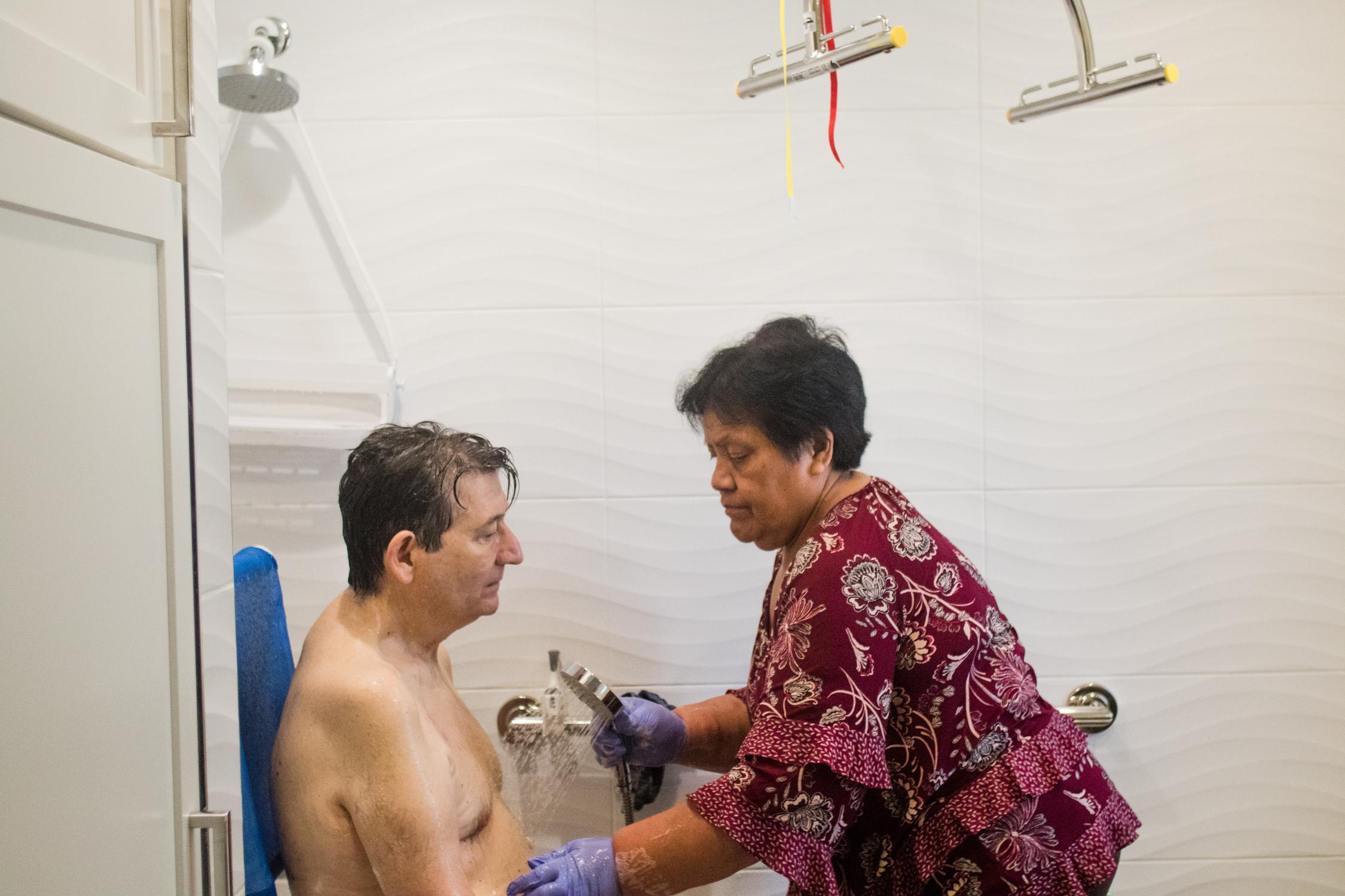 Jon Ferraiolo's caregiver Elisapesi Tautakitaki gives him his daily shower on May 9, 2018.
