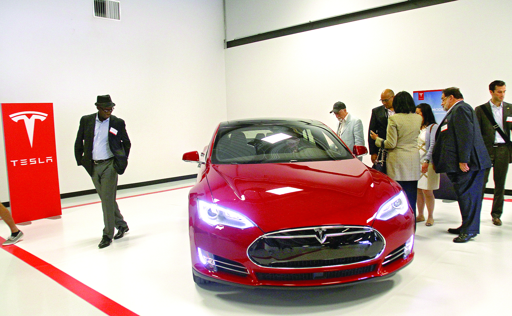 Babacar Diagne, ambassador to the Republic of Senegal, far left, along with ambassadors from Barbados, Grenada, Oman, Luxemborg and their staff   admire the Tesla cars in the company's showroom at its headquarters in Palo Alto on March 31, 2015, during a three-day technology tour ofSilicon Valley.  Photo by Veronica Weber.