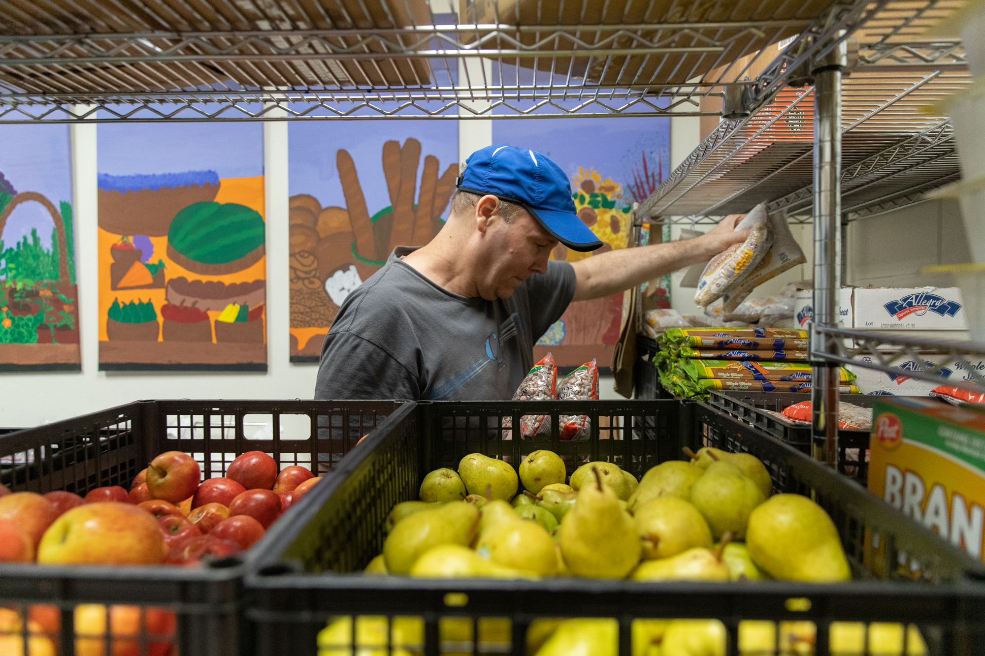 """Tim Purdy, a volunteer with Samaritan House, grabs some rice and beans from the North Fair Oaks facility's """"food pharmacy,"""" which provides foods tailored to help diabetic patients control their blood sugar levels. (Photo by Magali Gauthier/The Almanac.)"""