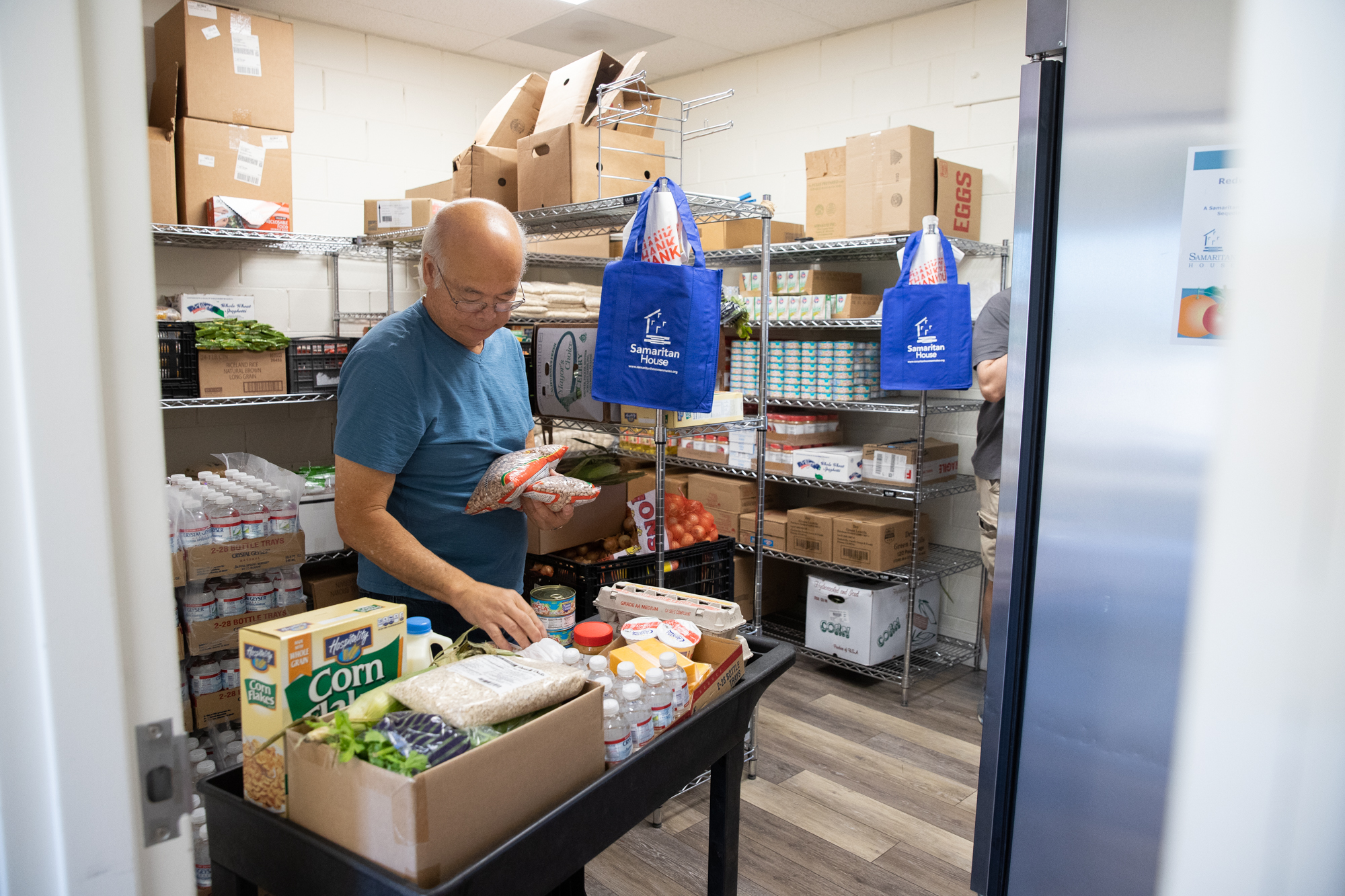 Ricky Neill, a volunteer with Samaritan House in Redwood City, prepares a food cart for a client at a food pharmacy in North Fair Oaks. (Photo by Magali Gauthier/The Almanac.)