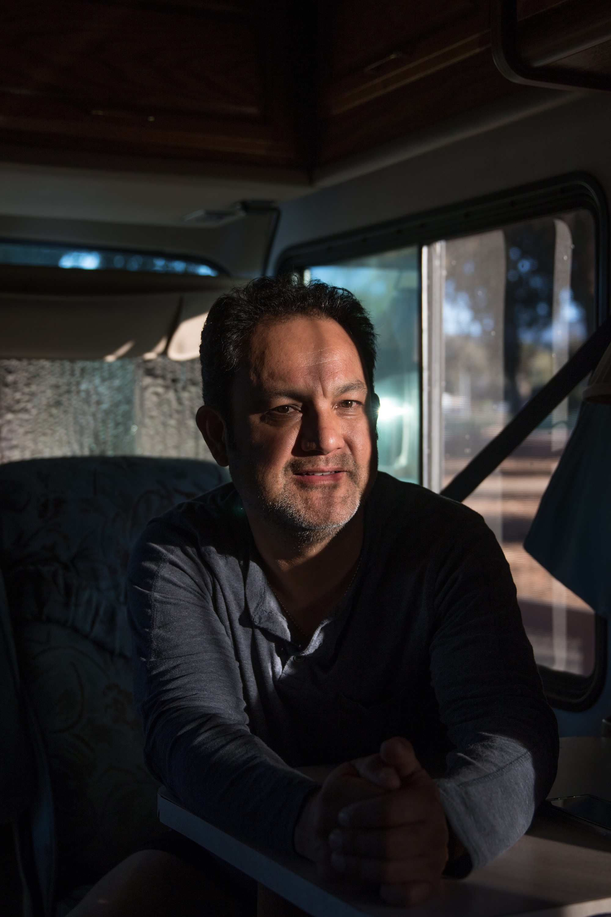 Arturo Torres, 48, sits in his RV parked on El Camino Real. He works eight to 12 hours Monday through Friday on numerous construction projects in Silicon Valley, including at Apple, Facebook and in Stanford Research Park.