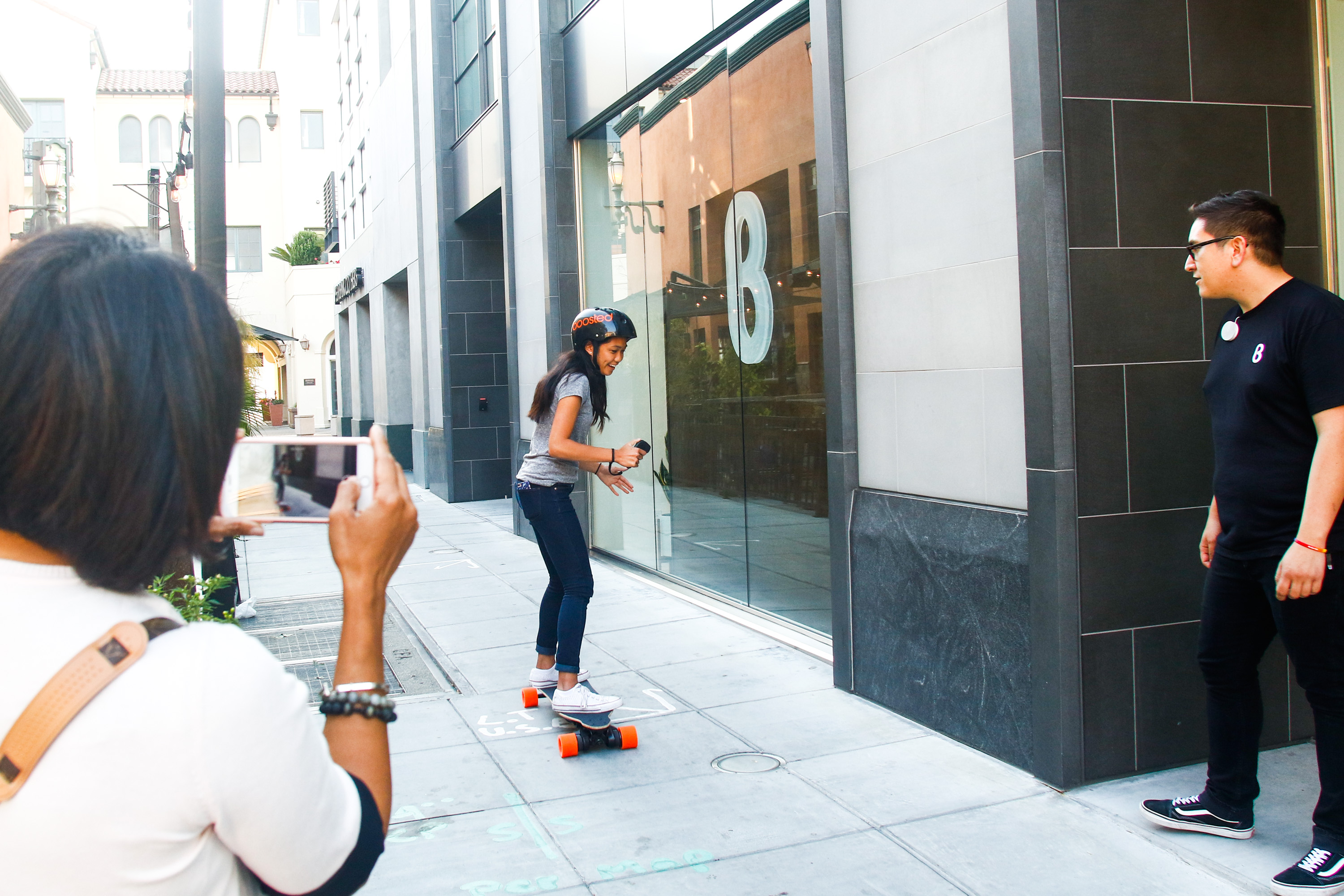 Maria Sit, takes video of her daughter Maile Sit, 14, as she tries out the Boosted Dual electric skateboard at the b8ta store in Palo Alto while Kevin Chu, a b8ta tester teaches her how to use the skateboard on Aug.17, 2017. b8ta encourages customers to test out and play with the numerous tech products for sale. Photo by Veronica Weber.