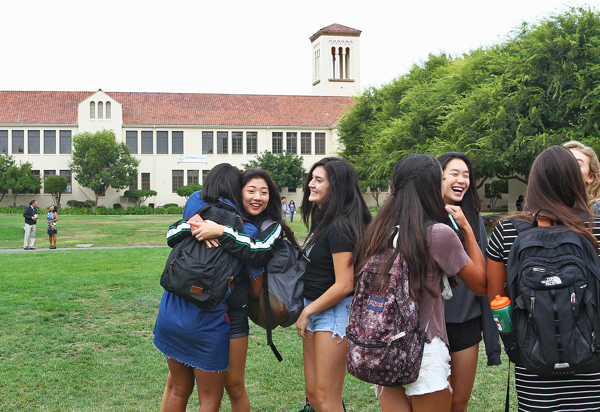 A group of girls hug and catch up with each other before classes begin on the first day of school at Palo Alto High School in 2016. Photo by Veronica Weber.