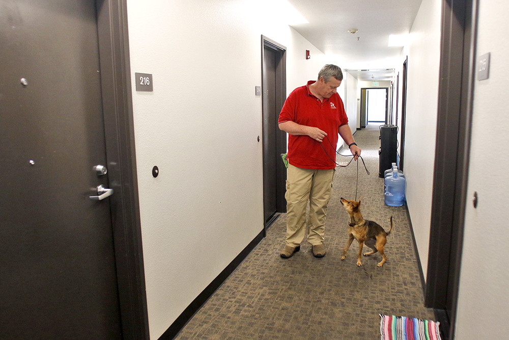 Jeff Tantzen, owner of Good Dog Bed Bug Protection, and Radar, a bed bug detecting dog, wait to enter a resident's room to check for bed bugs during a monthly inspection at the Opportunity Center on April 19.