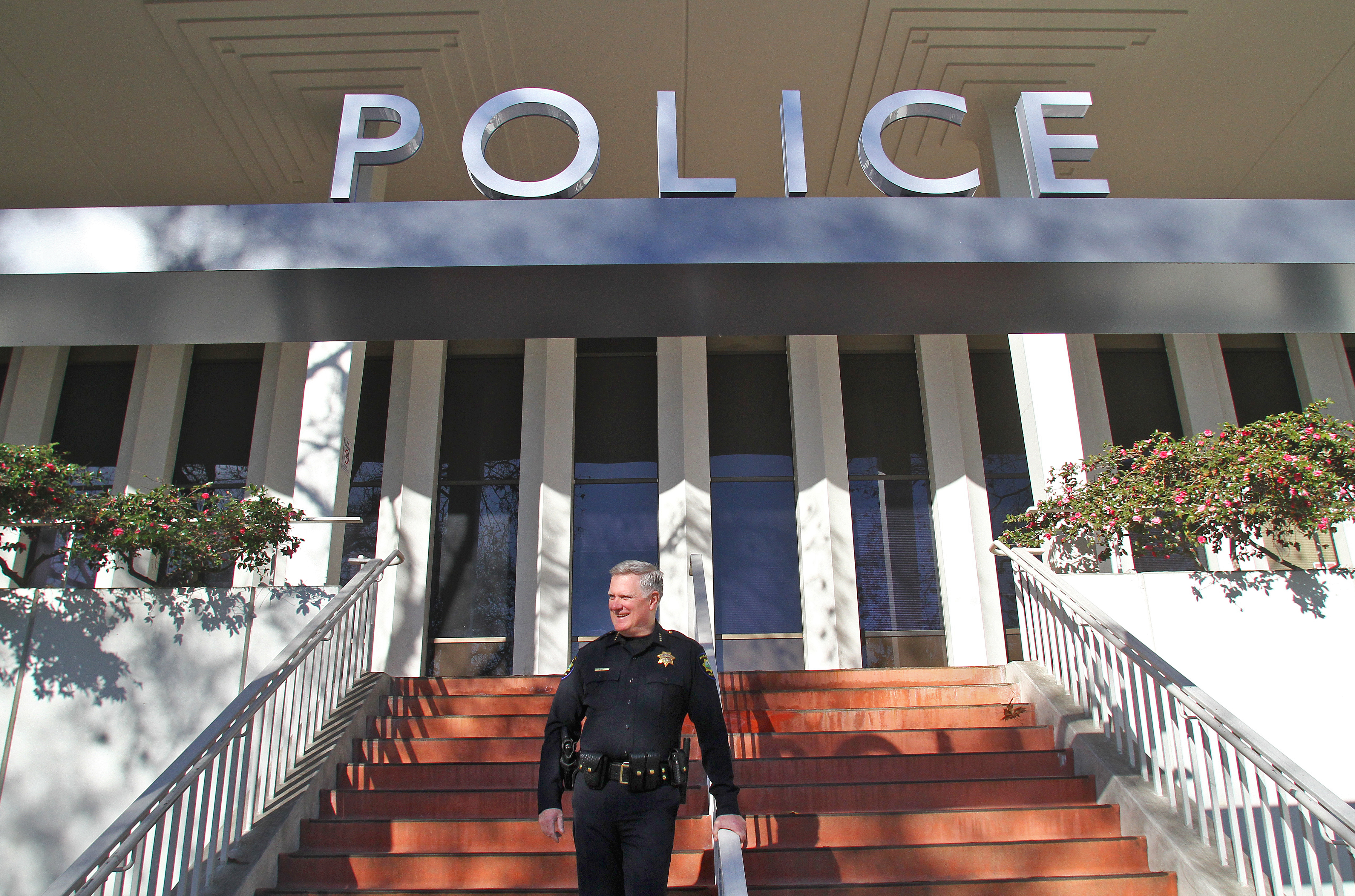 Dennis Burns, who retired as Palo Alto's police chief last month, stands in front of the Police Department headquarters onForest Avenuein Palo Alto. Photo by Veronica Weber/Palo Alto Weekly.