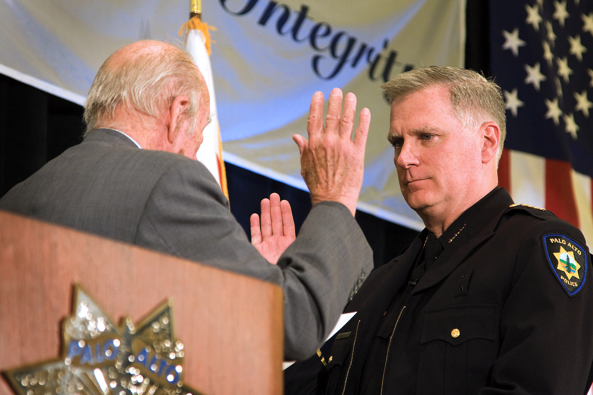Dennis Burns, right,is sworn in as Palo Alto's new Police Chief by former Secretary of State George Shultz onNov.30, 2009.  File photo/Palo Alto Weekly.