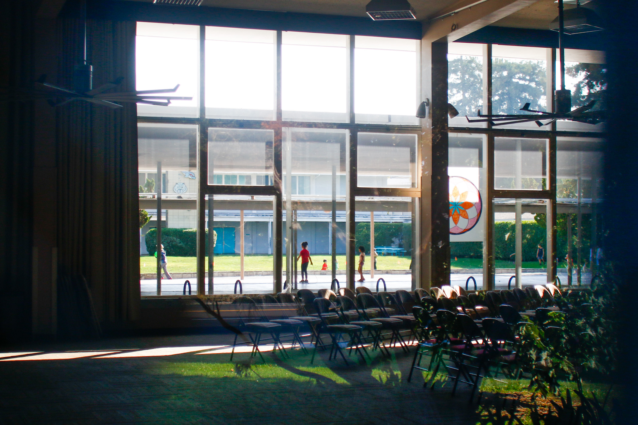 Children are seen playing outside through the windows of theauditorium where Sunday services are held for the Palo Alto Vineyard Church, one of three churches at the community center.