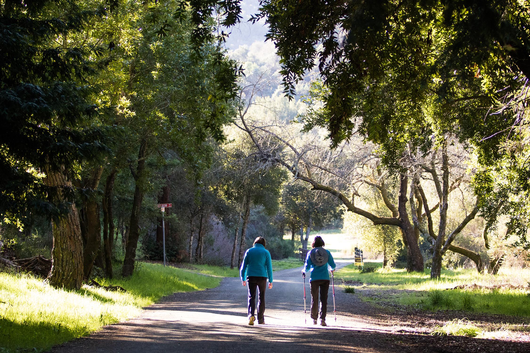 Hikers walk toward Wildhorse Valley in Foothills Park, the upstream area of Buckeye Creek.