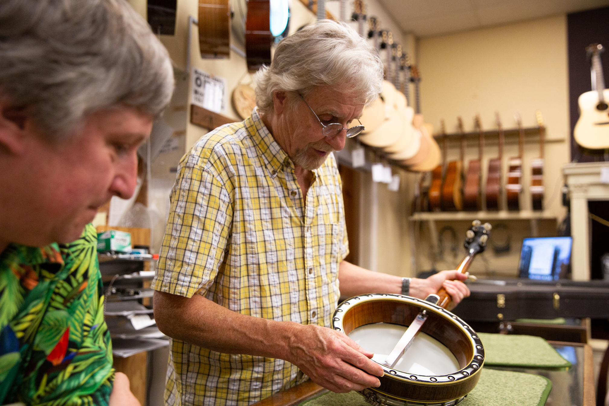 Richard Johnston, center, co-owner of Gryphon Stringed Instruments, takes a look at a banjo he and fellow co-owner Frank Ford made together in their Lambert Avenue shop.