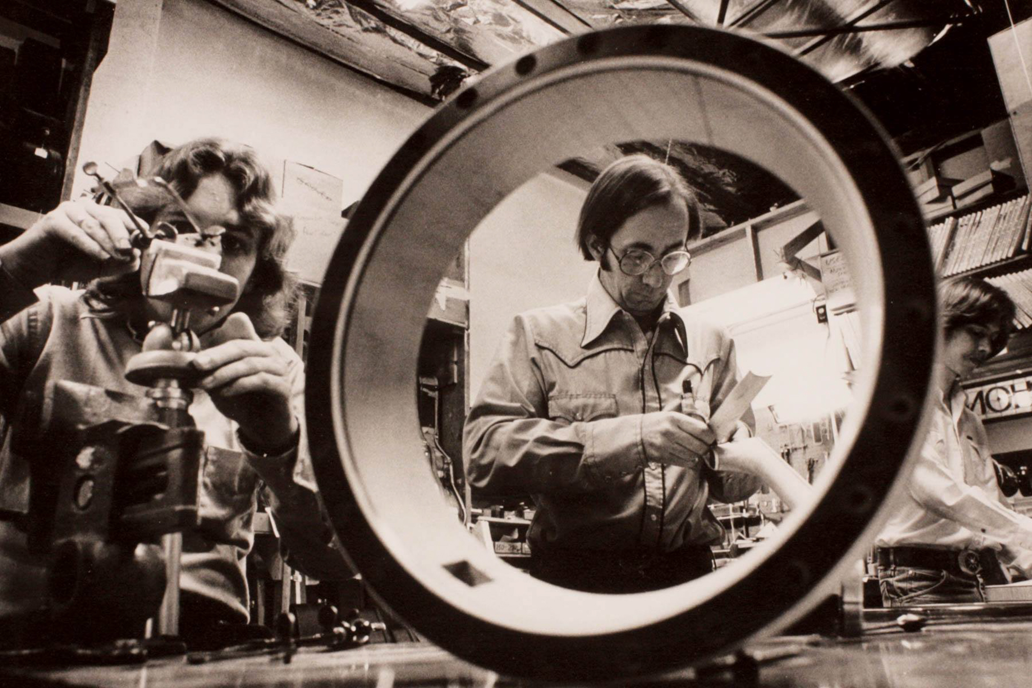 Frank Ford, center, and Richard Johnston, left, build a banjo together at Gryphon Stringed Instruments in Palo Alto during the 1980s. Photo courtesy Gryphon Stringed Instruments.