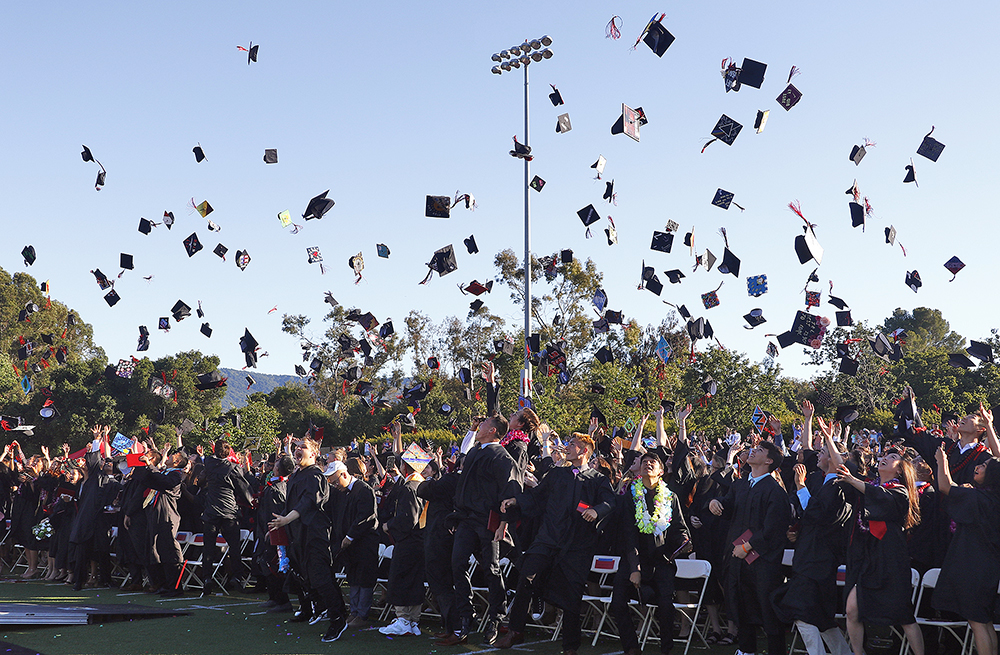 Gunn High School graduates toss their caps into the air after graduation ends on May 31, 2017. Photo by Veronica Weber.