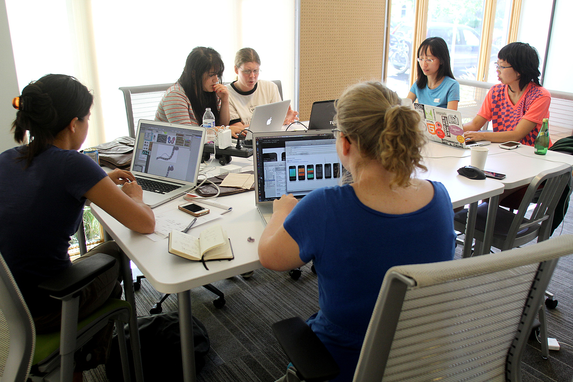 Sally Hermanto, far left,  Josie Zocca, second from left, Sara Neale, back center, Melissa Kelly, front center, Shannon Wang, second from right, and Brenda Jin, far right, work on the app at the incubator The Foundry in 2013.