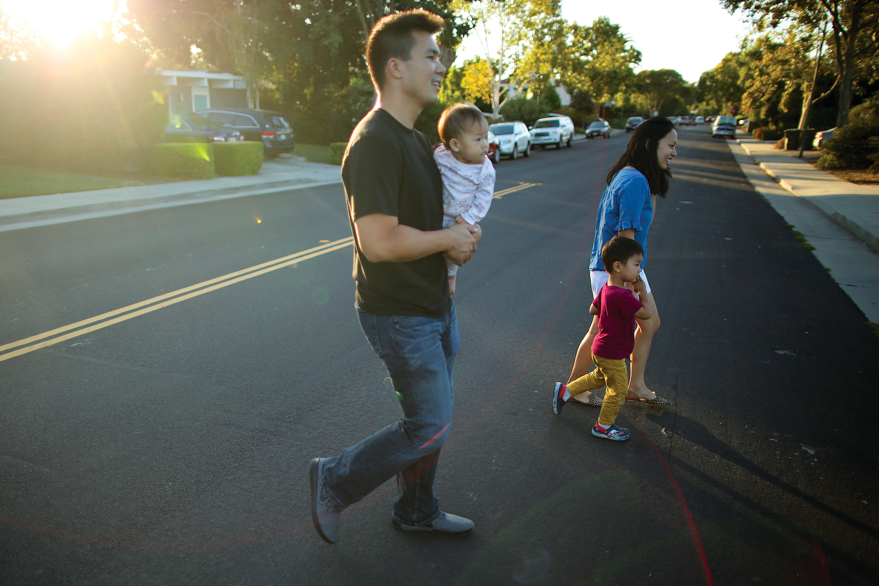 Parents David Liu and Angela Fan, with kids Zoe and Andrew, enjoy a walk along Greer Road in Palo Alto, to which they recently moved. Photo by Sammy Dallal.
