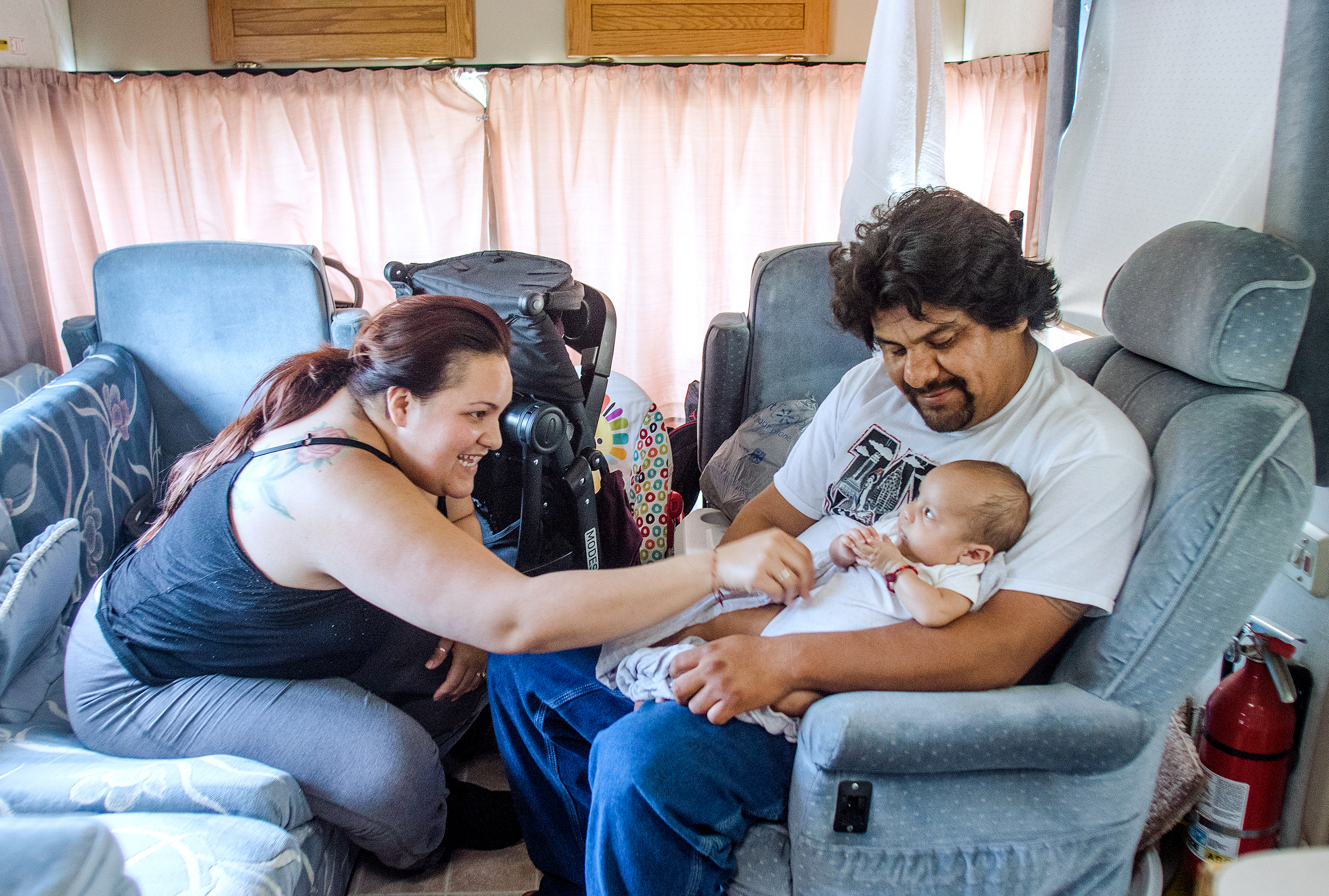 Alex and Miguel, of Paso Robles, spend time with their 4-month-old daughter, Mia, in their RV parked on El Camino Real.