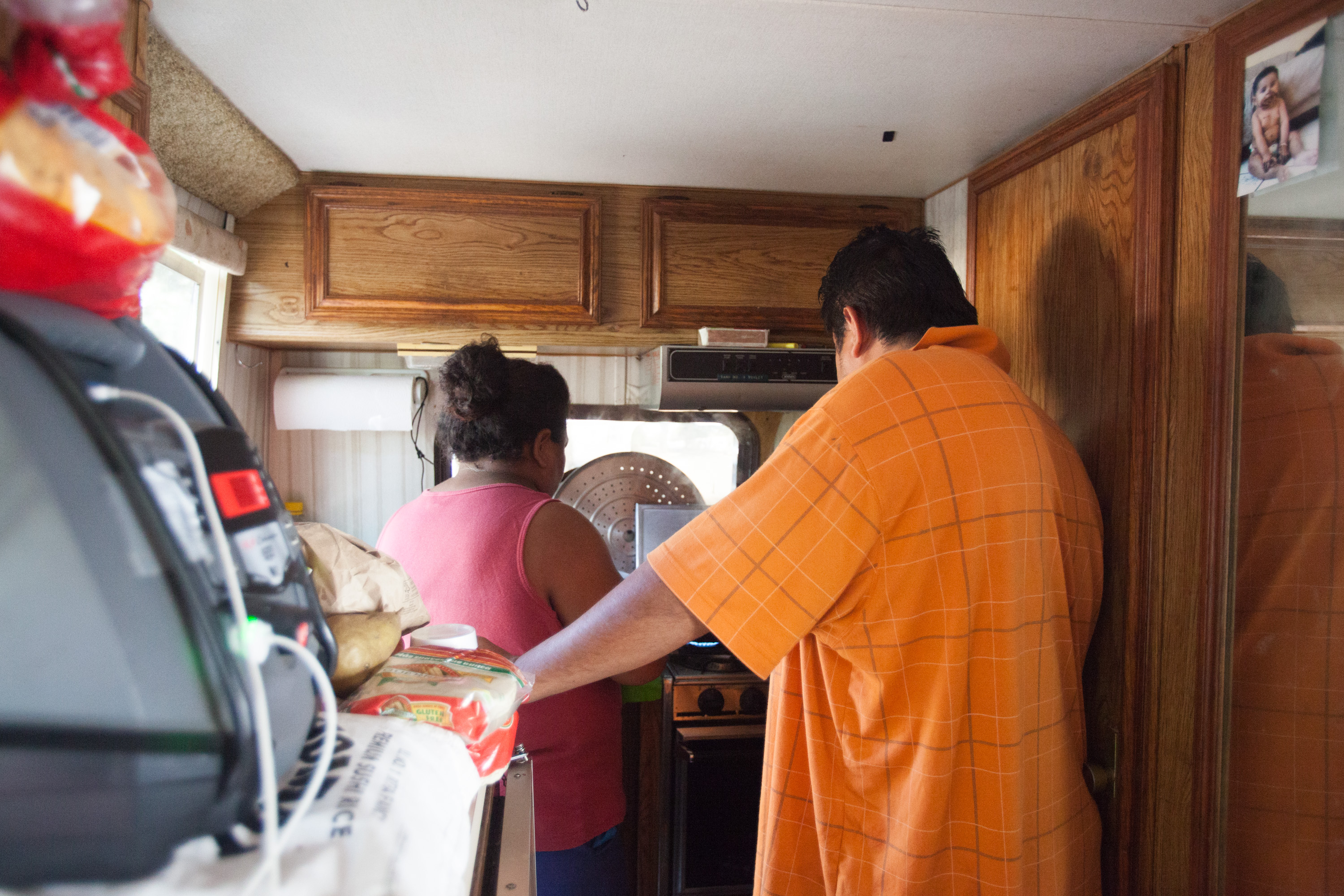 Noemi and her husband stand shoulder to shoulder in the cramped kitchen area of the RV as they prepare a meal, on August 30, 2017. Photo by Ana Sofia Amieva-Wang
