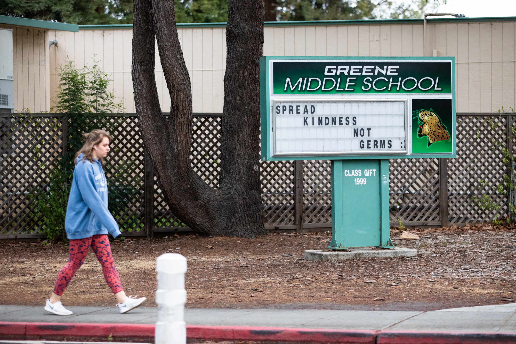 """A woman walks past a marquee outside Greene Middle School that reads """"Spread kindness not germs :)"""" in Palo Alto on March 18. Photo by Magali Gauthier."""