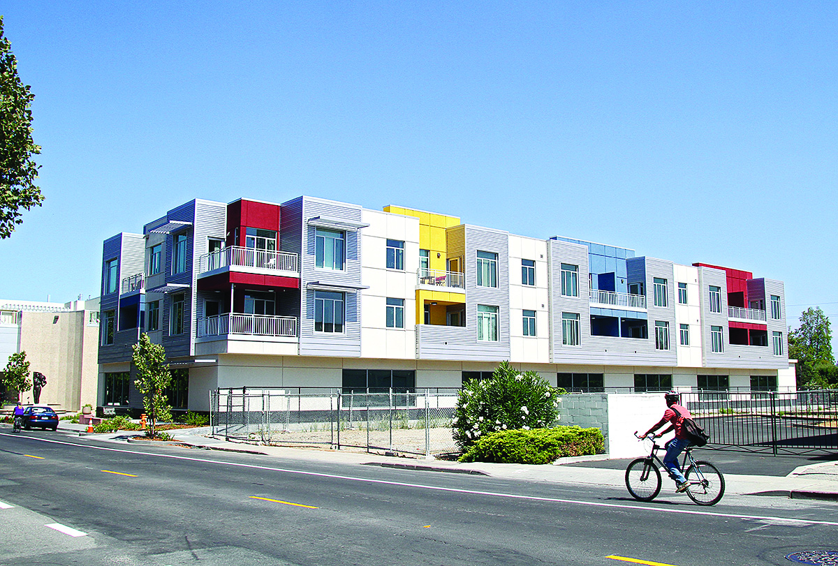 A bicyclist rides past the Park Plaza apartments at 195 Page Mill Road and Park Boulevard, a mixed-use development that features 82 apartments above commercial space. City leaders want to see denser housing complexes located near public transit -- in this case, the California Avenue Caltrain station.