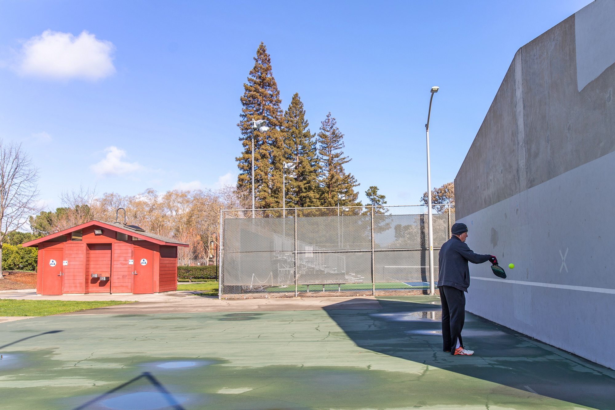 Kenneth Looney plays pickleball by himself at the Mitchell Park outdoor squash courts in Palo Alto on March 19. Photo by Magali Gauthier.