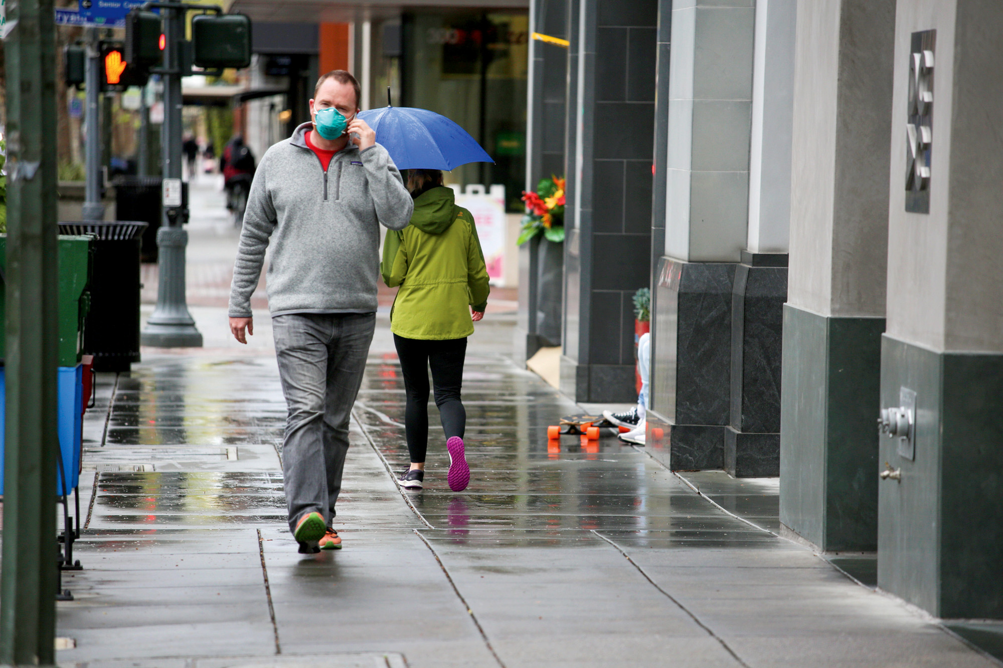 Pedestrians, one wearing a mask as protection from the coronavirus, walk down an unusually quiet University Avenue in Palo Alto after a shutdown order took effect on March 17. Photo by Sammy Dallal.