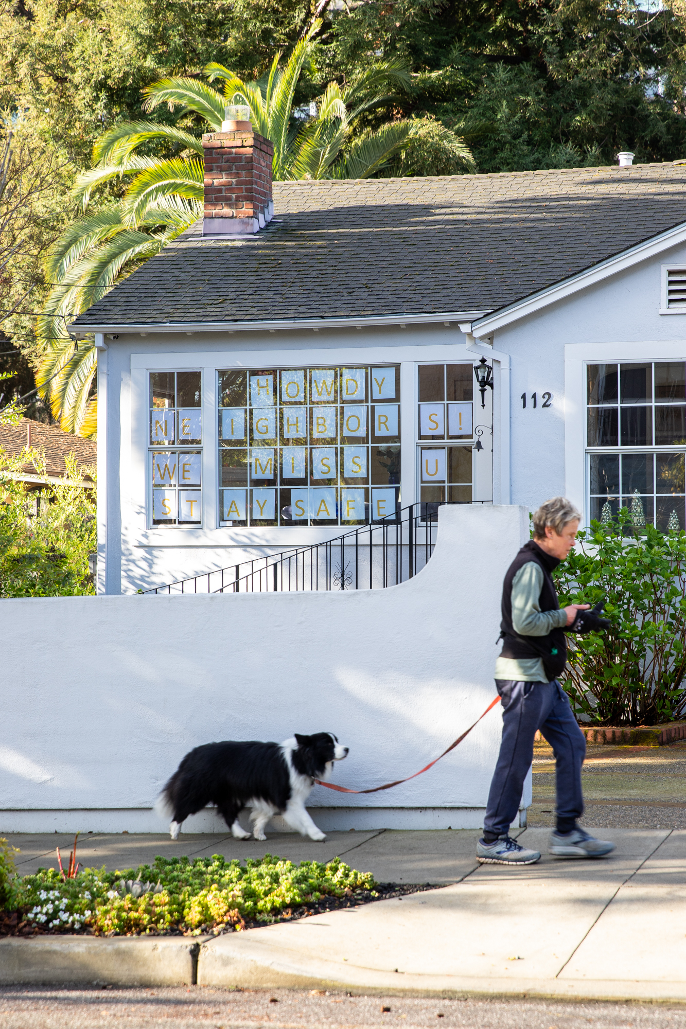 """A pedestrian and dog walk in front of house with the message """"HOWDY NEIGHBORS! WE MISS U STAY SAFE"""" in downtown Palo Alto on March 19. Photo by Magali Gauthier."""