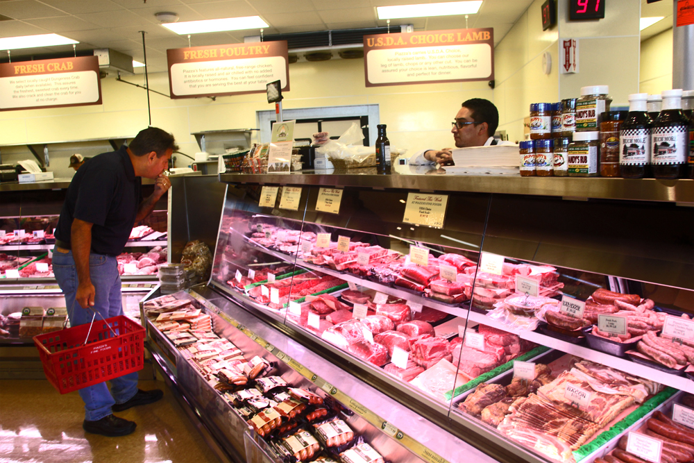 A customer examines the meat selection at Pizza's Fine Foods in Palo Alto in 2013. File photo by Magali Gauthier.