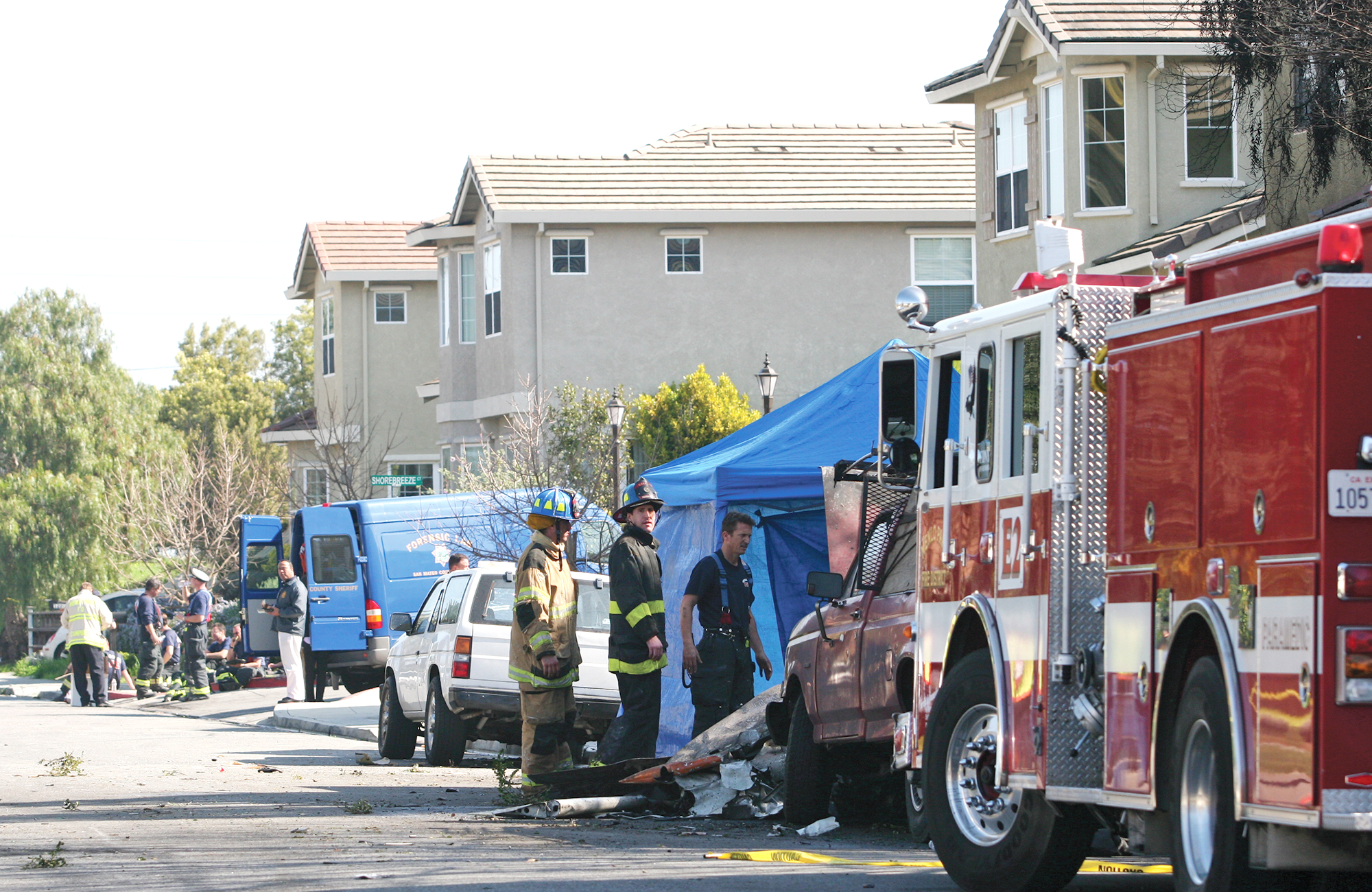 Members of the San Mateo County Forensics Team and firefighters from the Menlo Park, Palo Alto and East Palo Alto fire departments respond to a plane crash on Beech Street on Feb. 17, 2010. Photo by Veronica Weber.