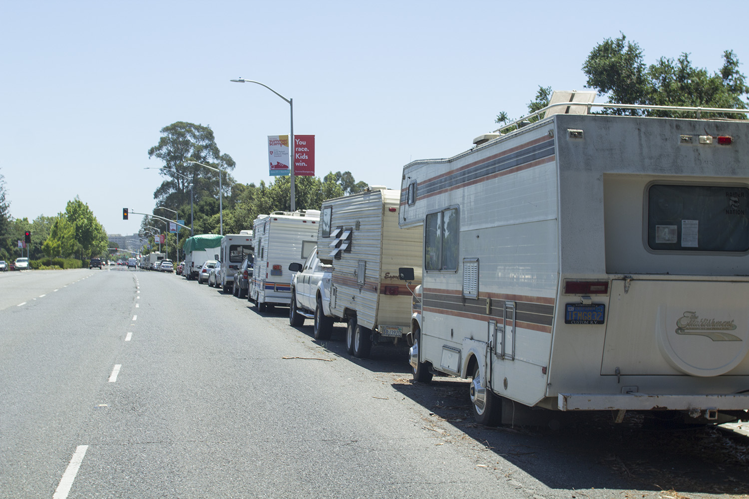 A long line of RVs and trailers parked along El Camino Real stretching from Galvez Street down to Stanford Avenue. Photo by Ben Hacker.