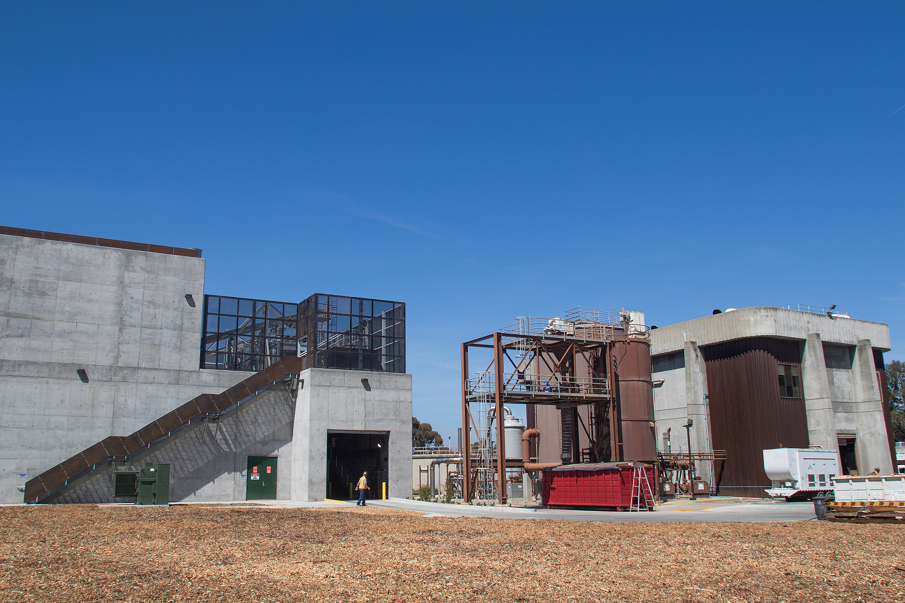 The city of Palo Alto opened its new sludge dewatering building, left, and retired the former incinerator building, right, in June. Photo by Veronica Weber.