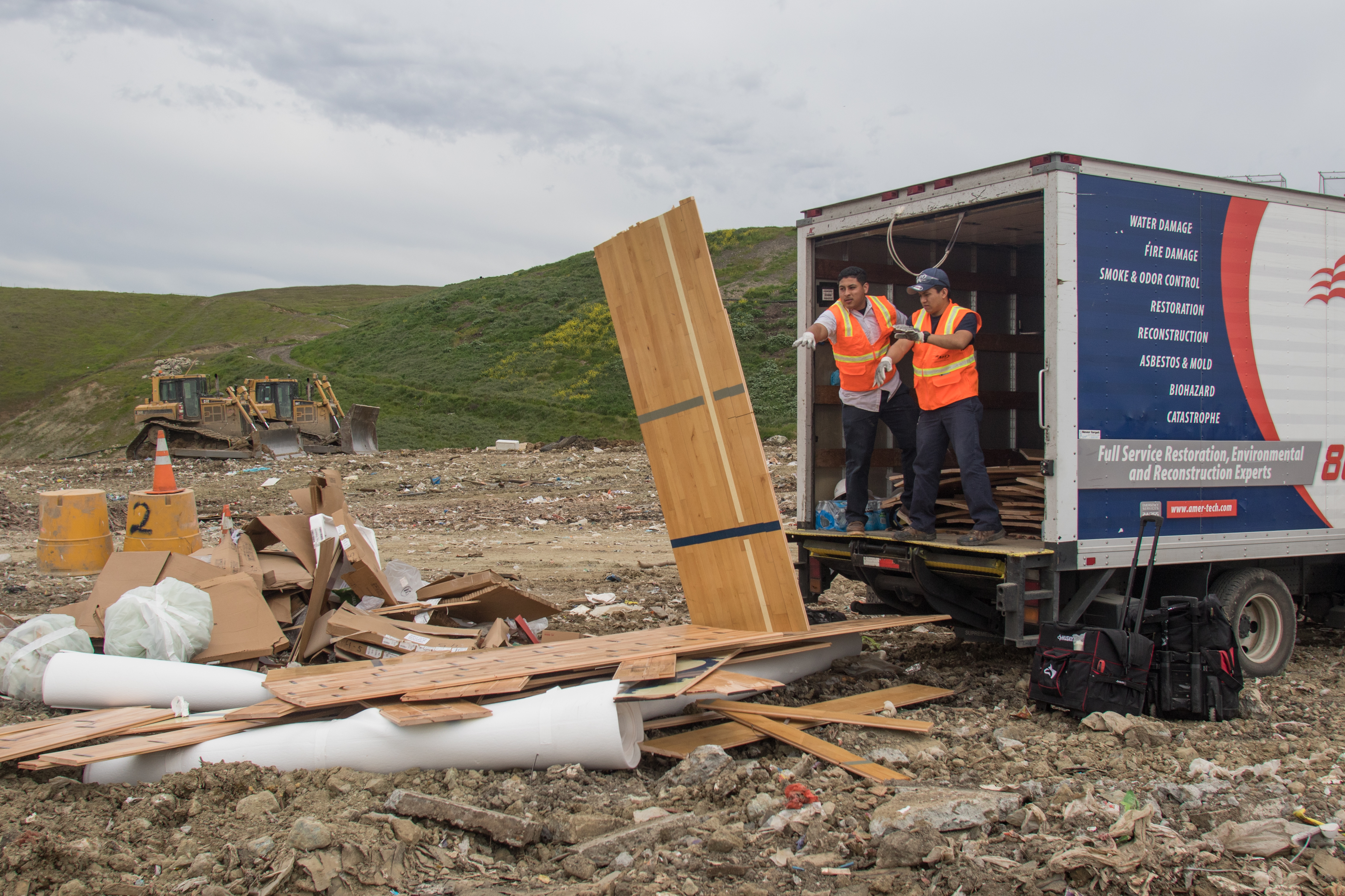 Demolition workers toss the remains of a middle school gymnasium wood floor into the landfill. The wood is treated with laminate and therefore unable to be otherwise recycled.