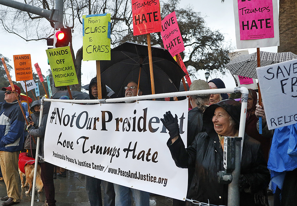 Protesters stand at the corner of El Camino Real and Embarcadero Road during a rally hosted by the Peninsula Peace and Justice Center following the inauguration of President Donald Trump on Jan. 20, 2017. Photo by Veronica Weber.