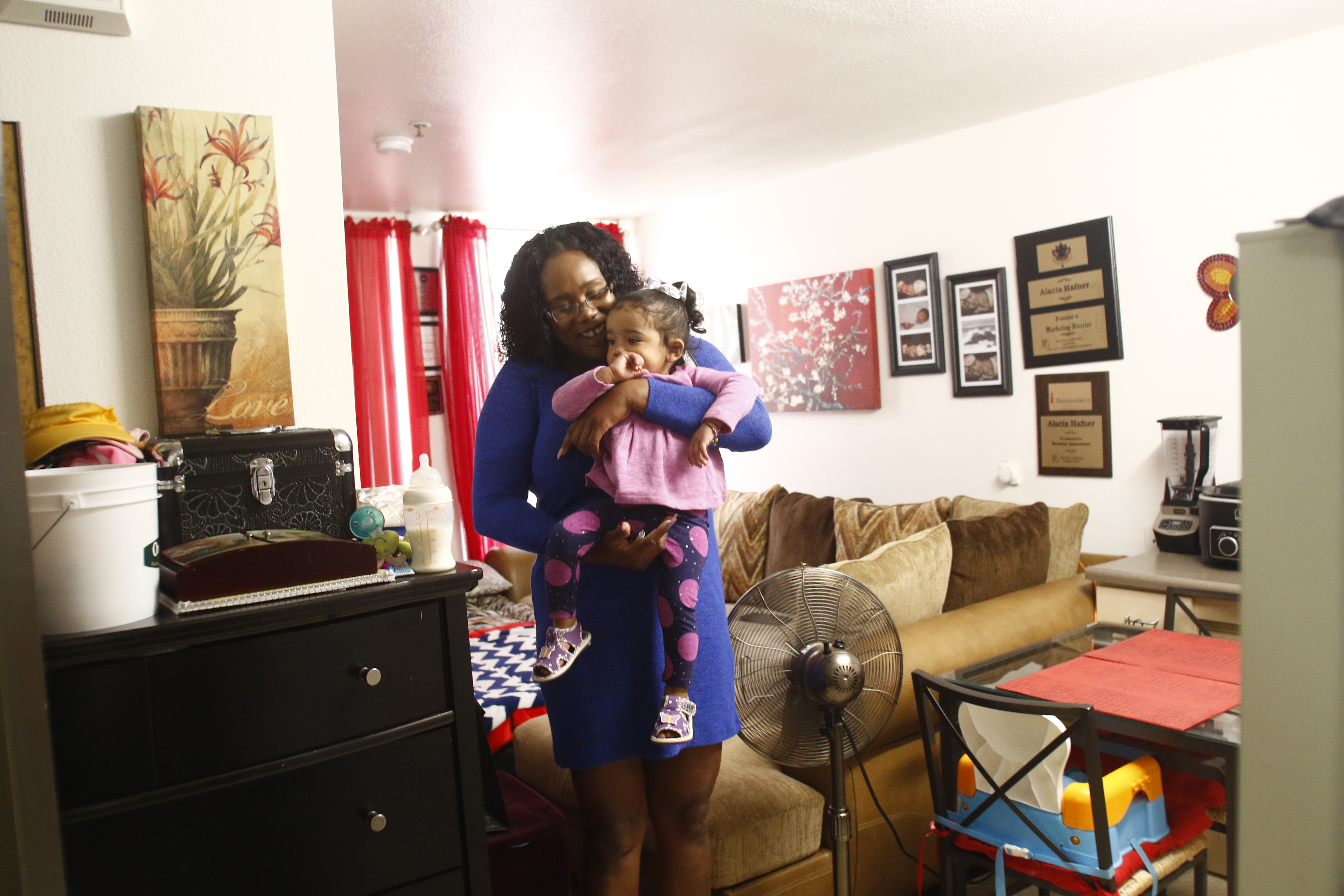 Alacia Hafner plays with her daughter in their Opportunity Center apartment.