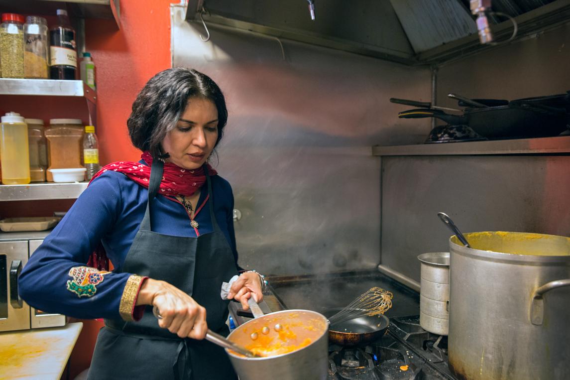 Zareen Khan cooks sweet semolina halwa in her Mountain View restaurant's kitchen. Photoby Natalia Nazarova.